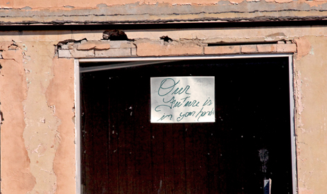 "A sign in a deserted shop window in downtown Superior, Ariz., reads ""Our future is in your hands."" Resolution Copper is proposing to build an underground mine about 10 miles east of town. Supporters say Superior needs high-paying jobs. Opponents worry that an eventual bust will wipe out any economic gains the mine may bring. Many of downtown Superior's merchants closed after the last bust. (Image: Mark Duggan)"