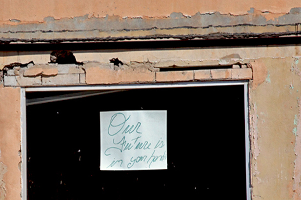 "A sign in a deserted building in downtown Superior, Ariz. reads ""Our future is in your hands."" A mining company has proposed building a new underground copper mine about ten miles east of town. Superior has been in an economic decline since other area copper mines closed. (Photo by Mark Duggan)"