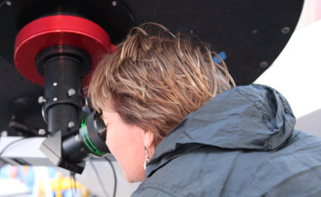 Woman looking through large telescope